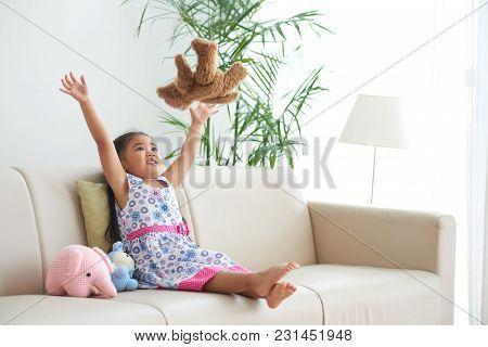 Lovely Little Girl Throwing Her Teddy Bear