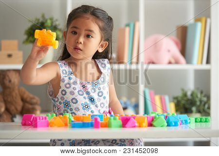 Little Girl Playing With Plastick Blocks At Table In Nursery Room