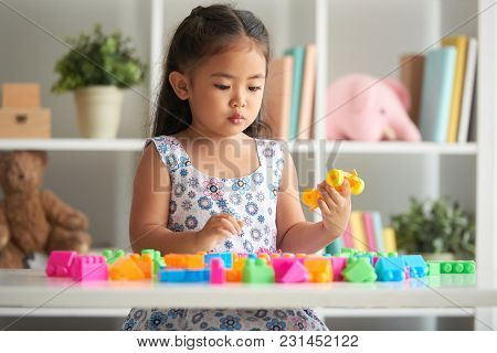 Adorable Little Asian Girl Playing With Her Toys In Nursery Room