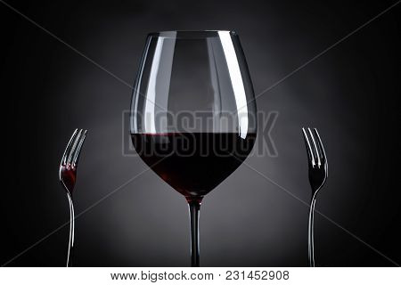 Glass Of Red Wine And Two Forks.