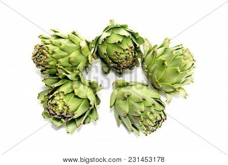 The Green, Fresh Artichokes In The Kitchen On A White Background Close-up