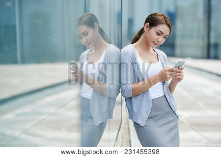 Pretty Young Vietnamese Busines Lady Checking Her Smartphone