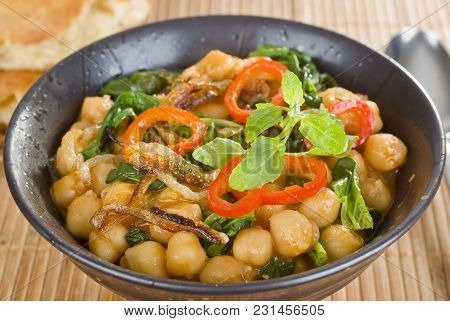 Indian Vegetarian Curry With Chickpeas, Spinach, Capsicums And Crisply Fried Onions.