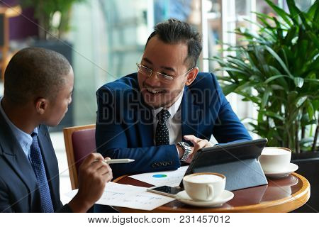 Cheerful Vietnamese Businessman Having Meeting With African-american Partner In Cafe