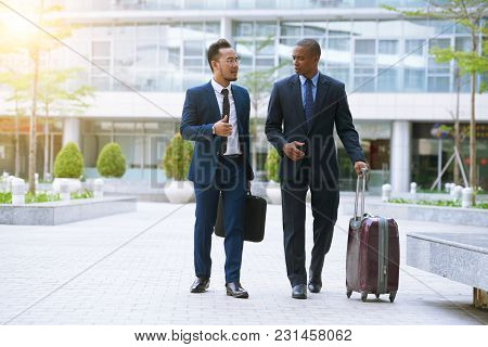 Talking Business People With Baggage Going To Airport