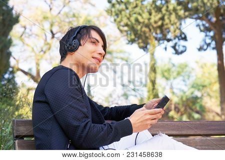 The Guy Is Sitting On The Bench, Using A Smartphone To Listen To Music On Headphones. Joyful Attract