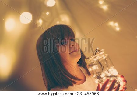 Girl Playing In A Teepee, Holding A Jar Filled With Christmas Lights
