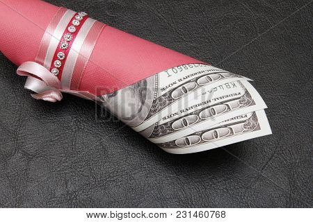 A Hundred Dollars In A Roll On A Black Background, Close-up. There Is A Place For Text