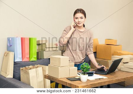 Young Happy Asian Online Seller, Business Woman, In Her Home Talking To Her Customer On Her Phone Wh