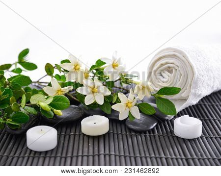 Spa setting on mat with roller towel, stones, candle, lying on gardenia