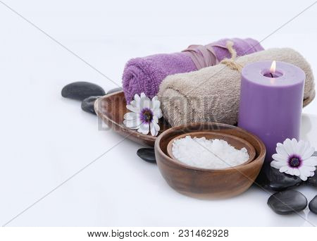 Spa concept with daisies, rolled towel in bowl with salt in bowl,black stones,candle