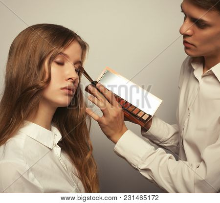 Beauty concept: Young beautiful   woman applying make-up by make-up artist