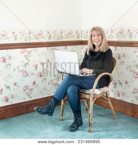 Mature Woman Sitting in Chair with Computer