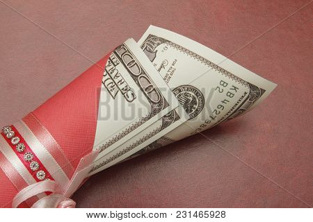 A Hundred Dollars In A Roll On A Red Background, Close-up. There Is A Place For Text