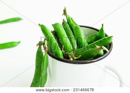 Fresh Green Peas In A White Metal Cup