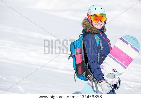 Image Of Female Athlete Wearing Helmet With Backpack And Snowboard In Winter Park During Winter
