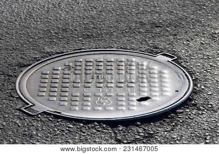 Paved Street Of The City.with A Metal Hatch For Waste Water .