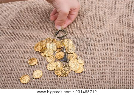 Hand Holding A Retro Styled Key Over Fake Gold Coins
