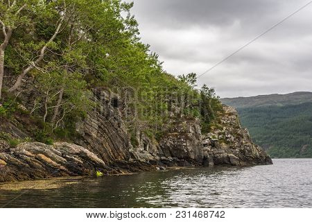 Lochcarron, Scotland - June 10, 2012: Green Trees Got A Foothold On Rocky Shoreline Of Loch Carron.