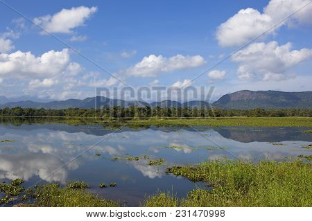 Mountains And Woodland With A Mirror Lake In Wasgamuwa National Park In Sri Lanka Under A Blue Sky W