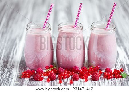 Three Jars Of Pink Berry Milkshakes With Straws On Old Wooden Table With Berries Next To Them.