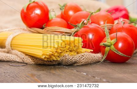 Long Pasta And Ripe Red Cherry Tomatoes On A Wooden Brown Table On A Beige Bag
