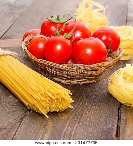 Long Vermicelli Macaroni With Ripe Cherry Tomatoes In A Basket On A Wooden Brown Table