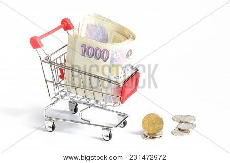 Red Shopping Cart With Czech Thousand Banknotes Inside And Coins Stack Isolated On White Background