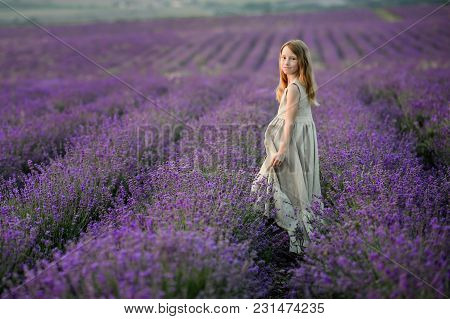 Beautiful Girl In Amazing Dress Walk On The Lavender Field.