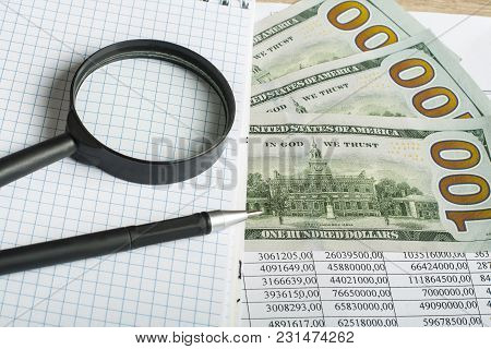 Magnifying Glass, Pen, Notepad And Money On Background Of Financial Documents. Financial And Budget