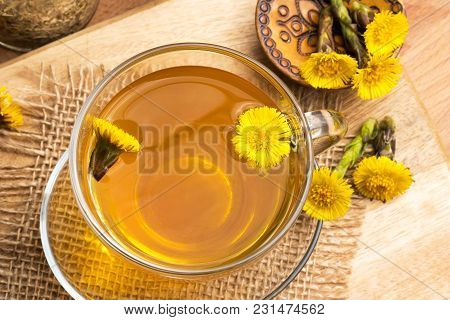 Coltsfoot (tussilago Farfara) Tea With Coltsfoot Flowers On A Wooden Table