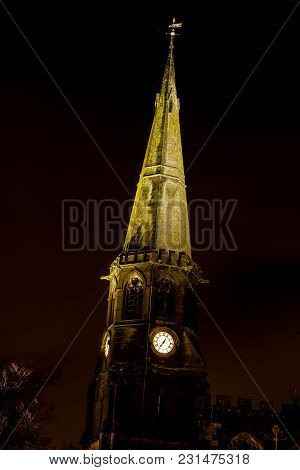 The Church Spire And Clock Lit Up At Night Time