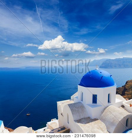 Traditional Blue Dome Of Church And Blue Sea Water Under Cloudy Sky, Oia, Santorini Island, Greece
