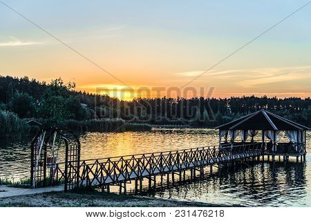 Footbridge With A Gazebo On The Lake Shore. Low Evening Sun At Sunset.