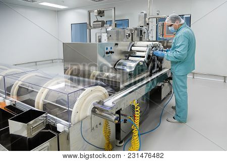 Pharmaceutical Technician In Sterile Environment Working With Equipment At Pharmaceutical Manufactur