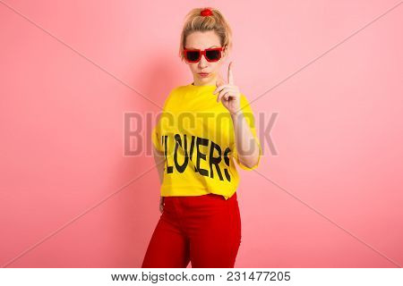Portrait Of Young Blonde Woman In Yellow T-shirt, Red Jeans And Sunglasses Holding Her Finger Up Iso