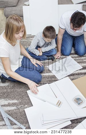 Dad And Son Are Staring At The Furniture Assembly Instructions Kneeling On The Carpet. Mom Chooses O