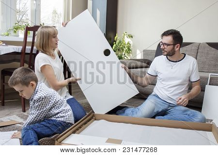 Family Twisting Of Furniture. Mom And Dad Are Folding Furniture. The Child Boy Carefully Reads The A