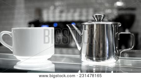 White Coffee Cups And Teapot On Glass Counter