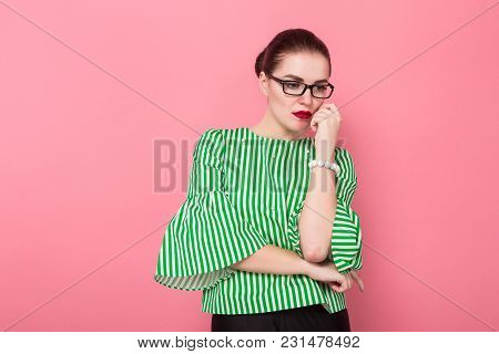 Portrait Of Attractive Businesswoman With Hair Bun In Striped Blouse And Eyeglasses Standing With Ar