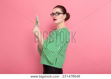 Portrait Of Businesswoman With Hair Bun In Striped Blouse And Eyeglasses Holding Fan Of Euro Bills I