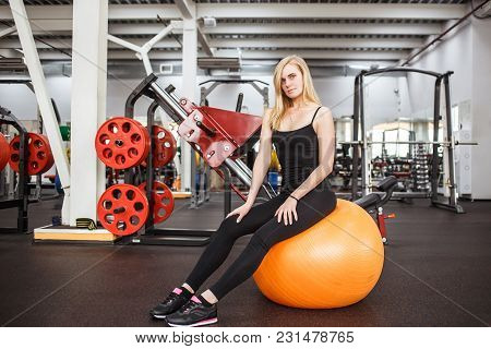 Young Sporty Slender Woman In Gym Posing On Orange Ball On A Background Of Gym Apparatus. Perfect Bo