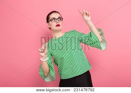 Portrait Of Attractive Businesswoman With Hair Bun In Striped Blouse And Eyeglasses Holding Fingers