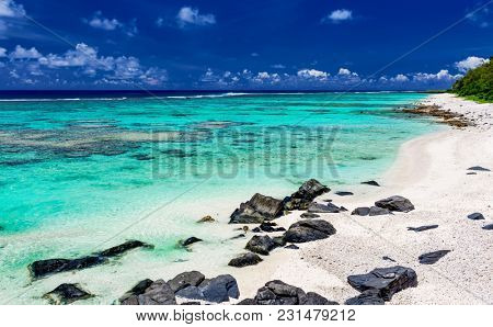 The most amazing beach with white sand and black rocks on Rarotonga, Cook Islands