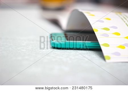 Magazine On The Table And Green Smartphone
