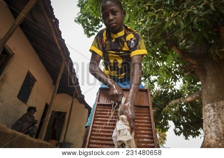 Nhacra, Republic Of Guinea-bissau - January 28, 2018: Young African Boy Washing His Clothes In A Was