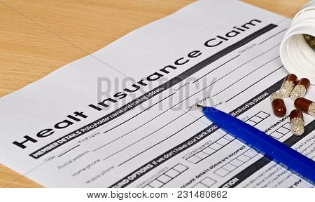 Healt Insurance Claim Form On A Wooden Surface. Next Is A Blue Fountain Pen And Pills
