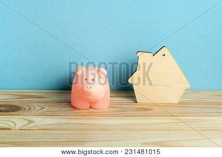 Pink Piggy Bank And Model House On Wooden Office Table . Financial, Budget And Property Concept.