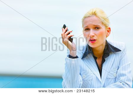 Outraged Business Woman With Cell Phone Leaning On Railing At Office Building