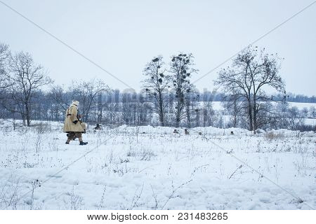 Soldier Walks Through A Snow-covered Field With A Rifle Concept Of A Second World War